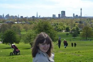 A portrait of Iris (the author) on a green hill. She is a brunette with straight sleek bob, fair skin and big smile. There are some couples walking behind her. London skyline is in the background.