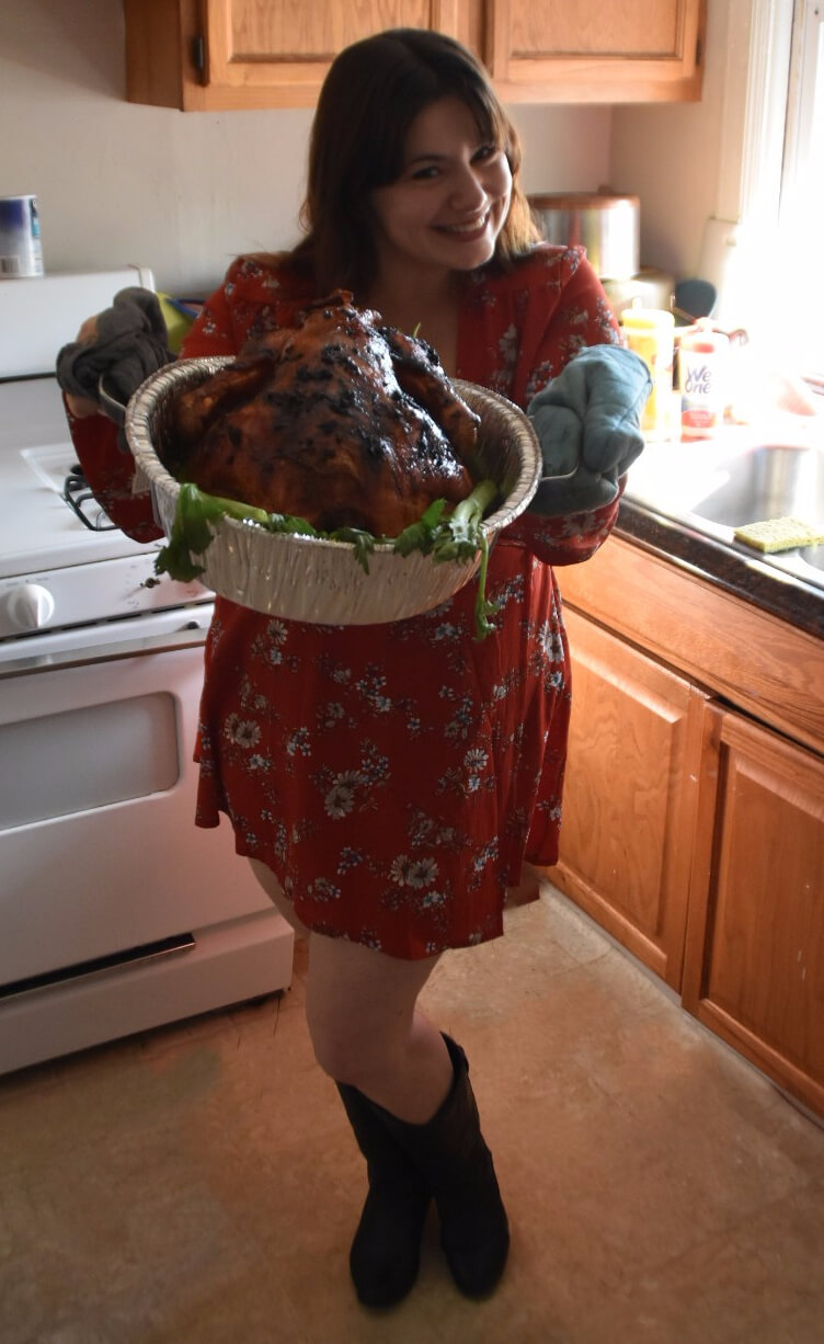 Iris Permuy holding the tray with the turkey ready to serve. She is smiling, she is wearing a floral orange dress, cowboy boots and teal oven gloves.