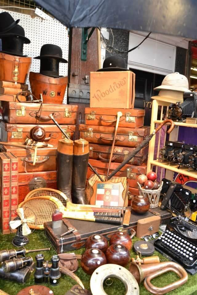 A market stall with old hats, tennis rackets, and a pile of leather suitcases, among other antiques.