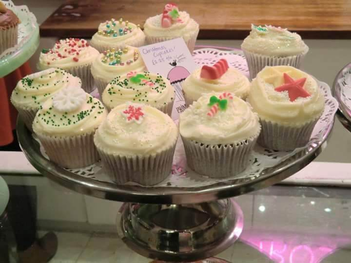 A silver plate full of cupcakes with white frosting and Christmasy sprinkles.
