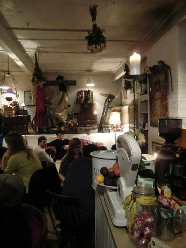 A dark picture of a crowded place with an antique weighing scale and a coffee grinder at a counter to the right, two mannequins wearing vintage clothing, a bike and some suitcase by the back wall, and a dry flower bouquet hanging from the ceiling, among other unrecognizable objects.