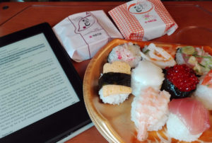 Train tray table displaying an electronic reader, a plate with assorted sushi, and two momiji manju cakes still on their wrapper.