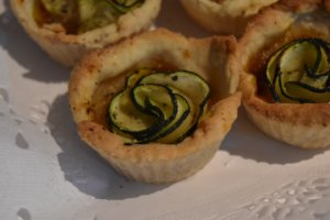 Small tart with a zuccini slice in the middle, shaped as if it were a flower.