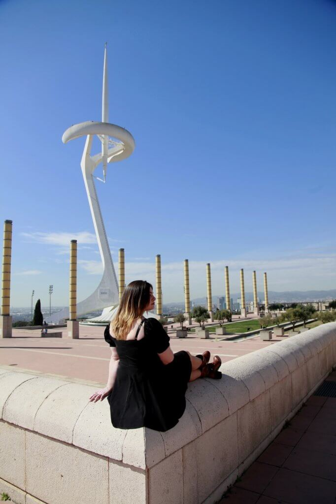 Iris is sitting on a stone lookout, overlooking the Montjuic Communications Tower, a tall white and pointy structure.