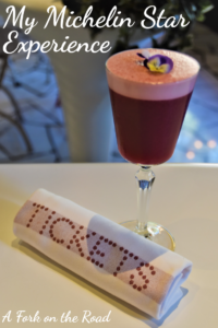A red cocktail with a purple flower on top, next to a napkin with the name Tickets written on it