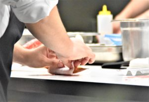 Male hands preparing some food in a bright kitchen counter.