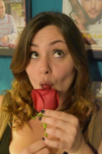 Iris is eating a red round candy from a red rose, and in doing so she makes a goofy face