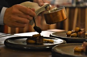 A male right hand pours some brown sauce over a piece of meat. On his left hand, his holding a small copper pot.