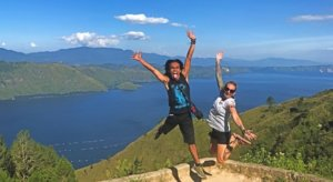 Carly and Agung jumping at the top of a green mountain with a view of the blue ocean and more green mountains in the horizon