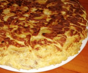 A tortilla de patatas fully cooked. It looks like a pie.