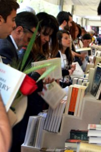 Many people browsing books in a street stand. One person has a red rose in their hand.