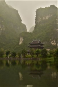 A pagoda on a little island on a lake surrounded by tall green mountains