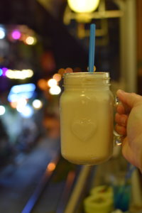 A jar with a vanilla milkshake-looking beverage held on a balcony over a railway.