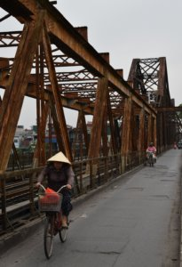 Long Biên bridge, a rusty iron bridge being crossed by a woman on a bike wearing a cone-shaped hat.