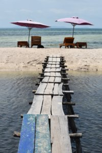 A rustic wood platform crossing a river and leads to a thin white sand beach with two umbrellas