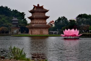 A pagoda in the middle of a river, and in front of it, a huge fake pink lotus flower.