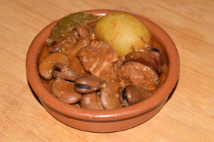 A clay casserole with an individual portion of michirones