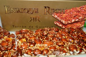 A golden rectangular box with the Enrique Rech logo and, in front of it, an almond bar coated with honey and sesame.
