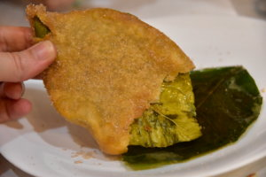 Paparajote, a leave covered in fried dough. The tip of it is bitten.