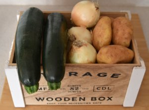 A wooden box with zucchinnis, onions and potatoes