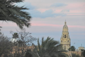 The tower of the cathedral in the horizon, against a pink and blue sky and surrounded by palm trees