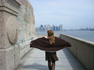 Iris, on the bottom of the Statue of Liberty, walks with her arms extended towards the city, in a way that her brown jacket looks like her wings.