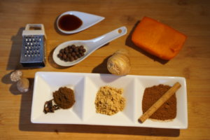 A small grater with pure nutmeg next to it, a spoon with allspice, another with vanilla extract, a piece of baked pumpkin, a piece of fresh ginger, some grounded cloves, grounded ginger and cinnamon in a three-compartment rectangular dish.