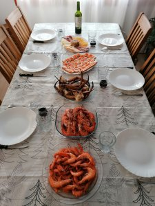 A table with read wine, a cheese and cold cuts platter, some salmon canapes, crab legs, prawns and shrimp.