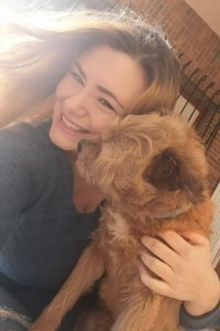 Miau, a small brown rescue dog, is sat on Iris lap and trying to lick her face while she smiles.