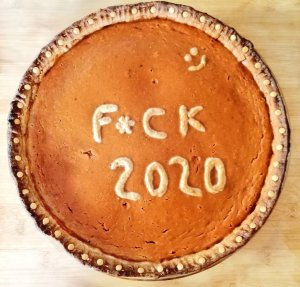 A sweet potato pie with a message written with dough in the batter: F*uck 2020.