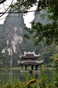 A shrine in the middle of a river that reflects the greenery of the tall and narrow mountains around it.