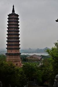 A very tall pagoda overlooking some greenery hiding shrines. In the background, a river.