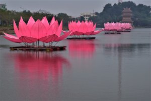 Three giant plastic lotus flowers floating in a river that leads to a pagoda.