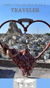 Pinterest post in which Iris is reclined on a heart-shaped bench with a view of Capadoccia, Turkey, and over the blue sky is written: Don't fall in love with a traveler. At the bottom of the post, A Fork on the Road's logo.