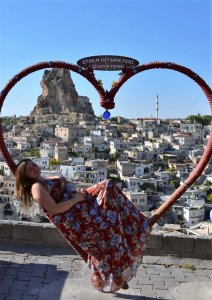 Iris is reclined on a heart-shaped bench with a view of Capadoccia, Turkey.