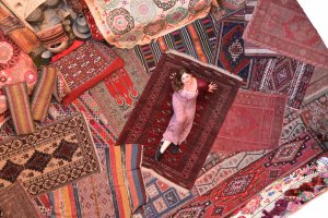Iris lays on a set of Turkish rugs of earthy colors.