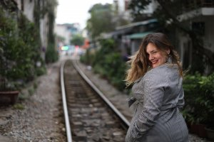 Iris walks on train tracks in Hanoi and she turns back, flipping her hair and amiling